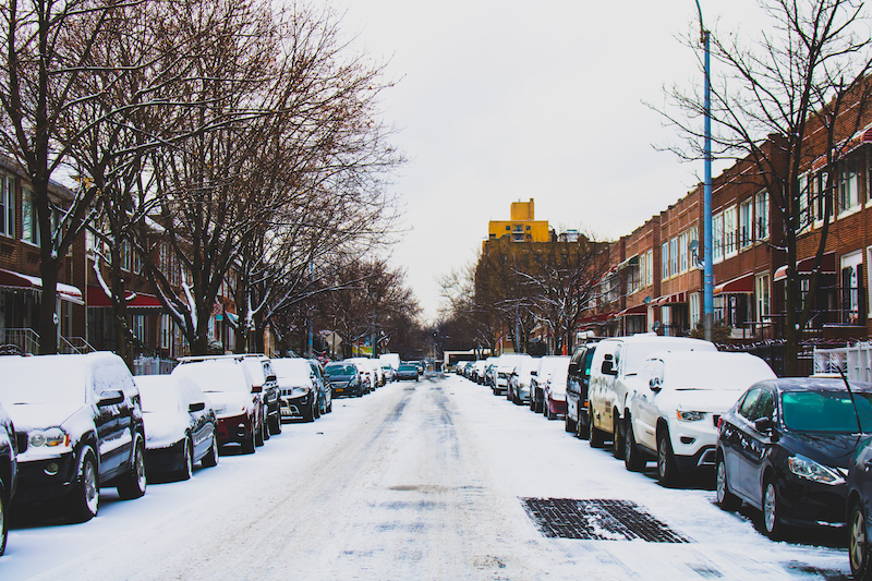 Snow Covered Road and Inline Parked Vehicles Between 2-storey Buildings Under White Sky